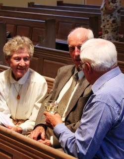 A group of people chatting in the pews after a church concert