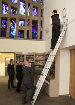 Alistair, in his best wedding suit, climbs a ladder to change a lightbulb in the narthex